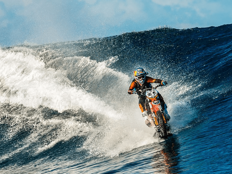 1 guy surfing ocean waves on a dirt bike 01