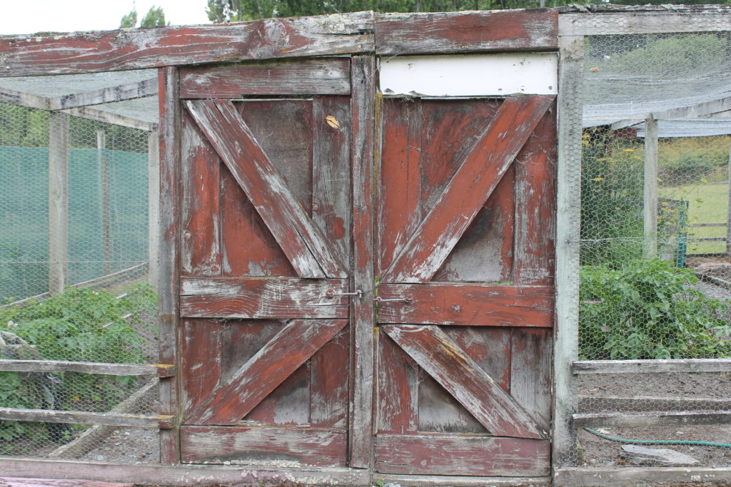 A rustic gate guards the entrance tot he caged kitchen garden.