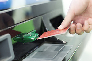 man insert credit card into ATM