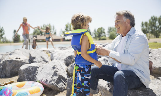 Grandfather putting lifejacket on grandson