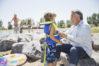 Grandfather putting lifejacket on grandson