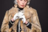 Senior rich woman posing with white gloves on isolated on black background. Serious lady looking at her hands.