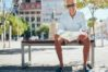 Happy senior male sitting on bench with a city map