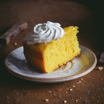 Pumpkin cake with whipped cream on plate. Square