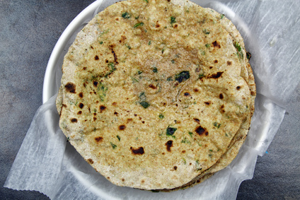 Overhead view of a stack of whole wheat and chopped spinach leaves Chapati or Roti or Tortilla