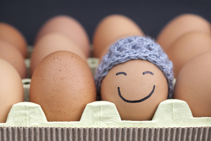 Smiling egg wearing a knitted hat souronded by blank brown eggs