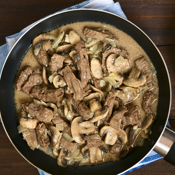 Beef Stroganoff in frying pan, a dish made of pieces of beef, mushroom and onion in cream sauce, photographed overhead with natural light
