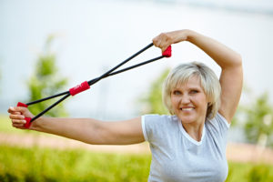 Sporty mature woman working out with resistance band