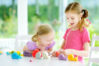 Two cute little sisters having fun together with colorful modeling clay at a daycare