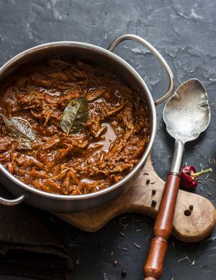 Slow cooker beef ragu. Crock pot braised beef on dark background. Delicious comfort healthy food