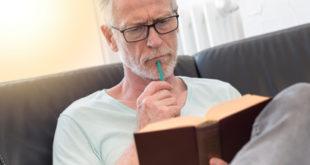 Portrait of thoghtful mature man reading a book, light effect
