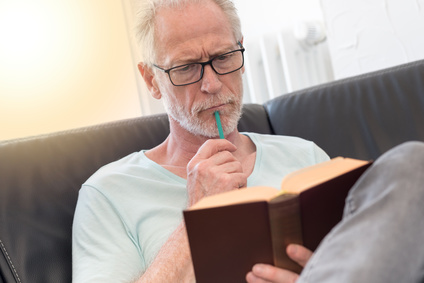 Portrait of thoghtful mature man reading a book, light effect