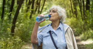 senior woman drinking water in the green summer  park.Healthy living concept