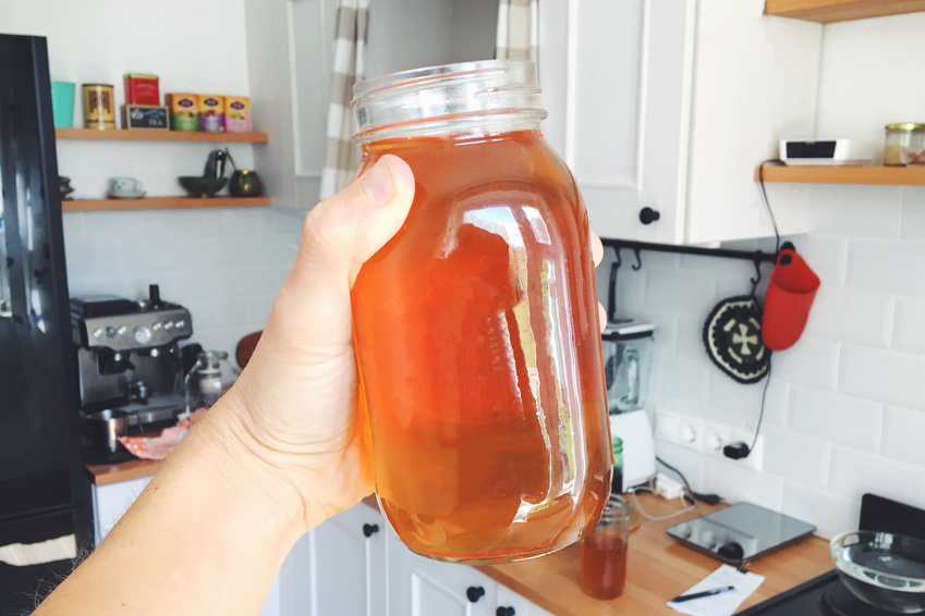 Hand Holding Jar of Homemade Organic Kombucha at House Kitchen. Healthy Hipster Drink.