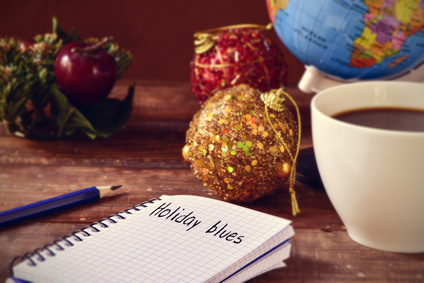 closeup of a notebook with the text holiday blues written in it on a rustic wooden table with some christmas ornaments, a cup of coffee and a globe