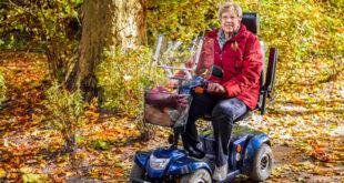 Seniorin fährt mit ihrem Elektromobil durch einen herbstlichen Wald spazieren  und lächelt in die Kamera