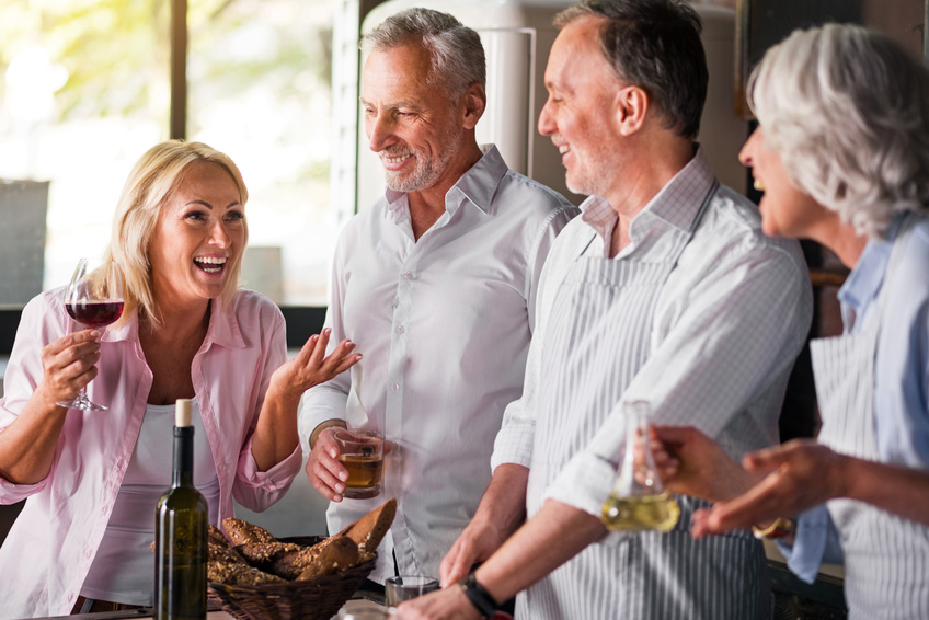 Emotional. Attractive blond middle-aged woman sharing a story making her friends laugh, while gesturing and having wine