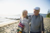 Smiling senior couple walking on sunny beach