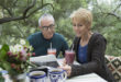 Couple drinking smoothies and reading newspaper on patio