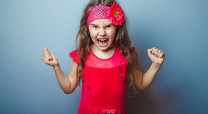 Girl European appearance haired child of seven in red bright dress on a gray background shouts, anger, anger