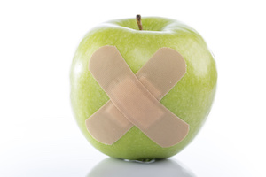 Green apple with a band-aid on white background