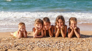 Five smiling kids enjoying on the beach