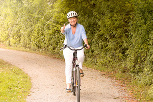 Fit healthy senior lady out cycling on her bicycle on a country road wearing a protective helmet and smiling happily at the camera in a healthy lifestyle concept