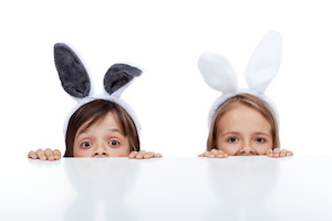 Kids with bunny ears peeking from beneath the table - waiting for the easter rabbit