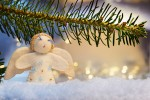 Image of a branch with felt angel on artificial snow and bokeh lights in background