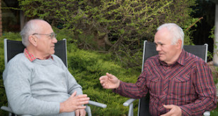 two senior men sitting in garden and descussing