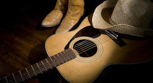 Spotlight on country guitar, boots and hat