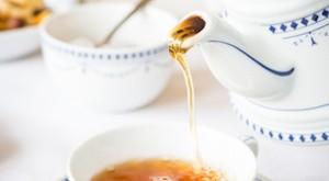 Tee wird ine eine Teetasse gegossen