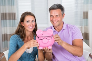 Portrait Of A Smiling Couple Holding Piggybank