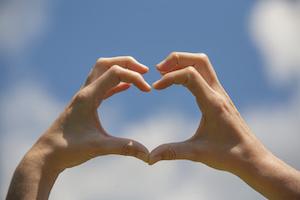 Heart shape hands on the blue sky