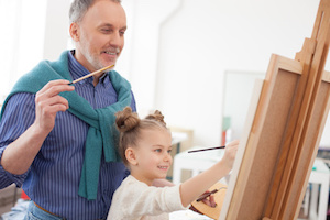 Skillful artistic family is painting together on canvas. The grandfather and the girl are smiling