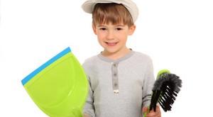 Portraitfoto eines kleinen Jungen der lächelnd mit Müllschippe und Handfeger da steht und offenbar mit saubermachen anfangen möchte...