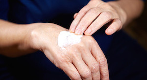 Senior woman with anti aging cream for hands