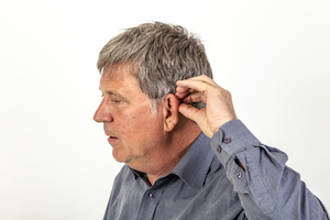 mature man  puts hearing aid in the ear