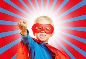 Kind als Superheld verkleidet mit geballter Faust vor einem Strahlen-Hintergrund