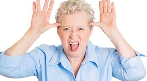 Closeup portrait of senior mature woman sticking out tongue at you, camera gesture, thumbs hands on temple, isolated white background. Negative human emotions, facial expressions, feelings, attitude