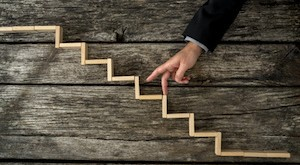 Businessman or student walking his fingers up wooden steps resembling a staircase mounted in rustic wooden boards in a conceptual image of personal and career development, success and aspiration.