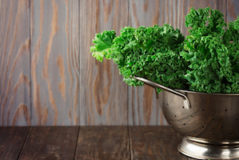 Fresh Green Kale leaves on rustic wooden background, selective focus