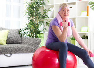 Senior woman exercising at home and smiling