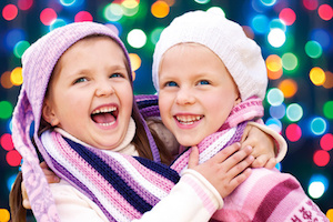 Cute little girls hugging and laughing together on Christmas Eve