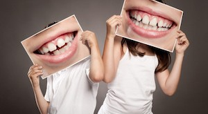 two children holding a picture of a mouth smiling