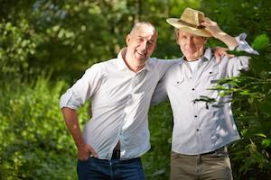 Männerfreundschaft zwischen zwei lachenden Senioren draußen in der Natur