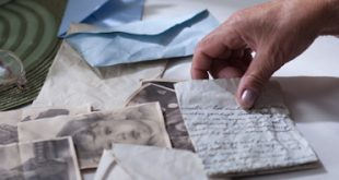Old widow is looking at souvenirs after dead husband