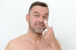 Middle-aged man applying moisturizer to his skin to ward off the signs of ageing in a skincare and pampering concept, head shot on grey