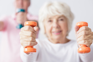 Elderly woman exercising with dumbbells.