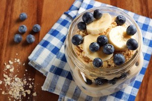 Blueberry and banana breakfast overnight oatmeal in a mason jar, with checkered cloth on wood